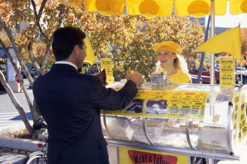 Man Purchasing Hot Dog at a Yellow Hot Dog Stand from Woman Wearing Yellow