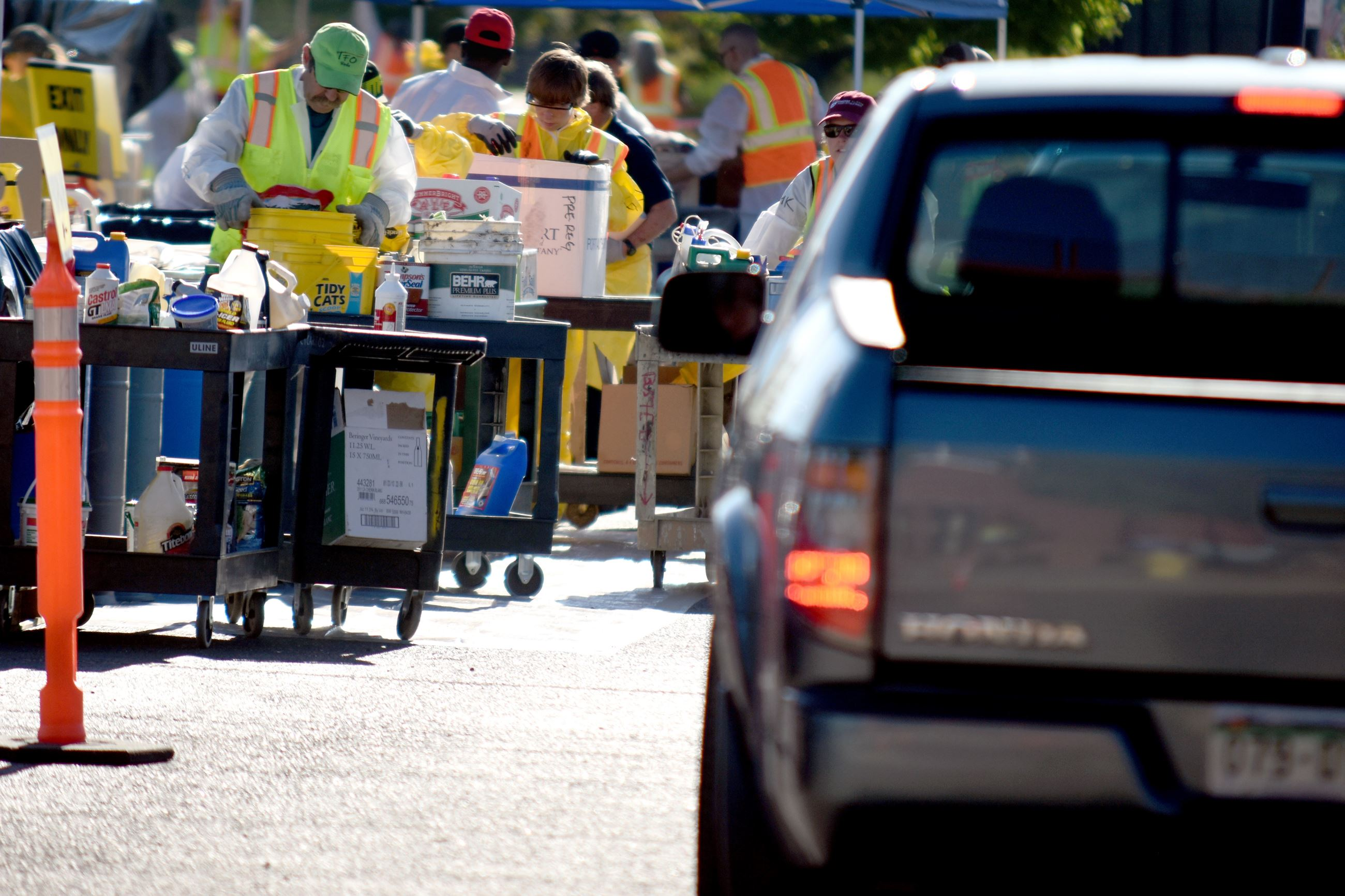 Workers in Neon Safety Vests Sorting Household Hazardous Waste at an Outdoor Collection Event