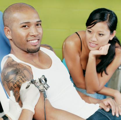 Man Smiling While Getting Tattoo and a Woman Watches