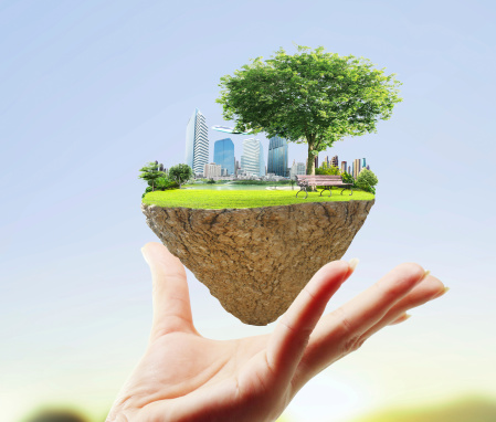 Land Use Stock Image of a Hand Holding a Floating Piece of Land with Buildings and Trees on It